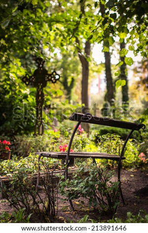 Old cemetery bench. Ancient cross in the background. Selective focus. - stock photo