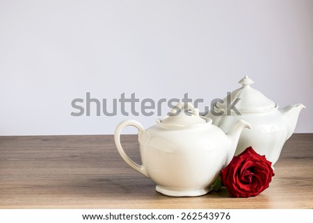 old ceramic teapot with rose,two ancient ceramic teapots white with a red rose on wooden table with white background, natural light - stock photo