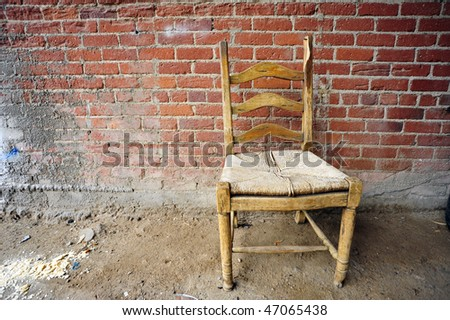 Old chair against textured brick wall background