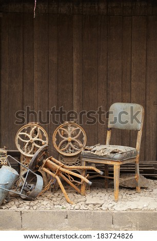 old chair and old wall in sun light - stock photo