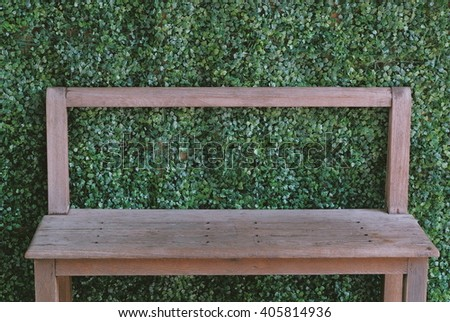 Old Chair at front wall with Green Plants in the garden - stock photo