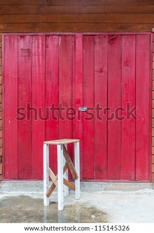Old chair in front of the old wooden red door. - stock photo