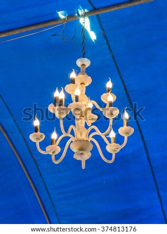Old chandelier is hanging on the ceiling of large tent. - stock photo