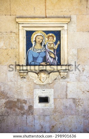 """Old charity box embedded in a stone wall with copy space. On the wall you can see the inscription: """"La limosina pi poveri prigioni"""" which means """"The alms for the poor prisoners"""". - stock photo"""