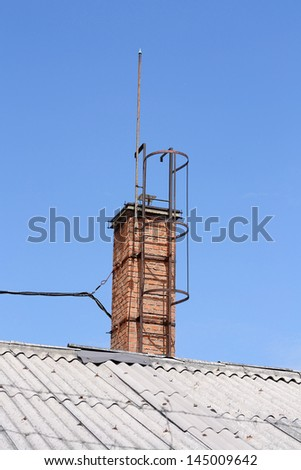Old chimney and rusty ladder on the roof - stock photo