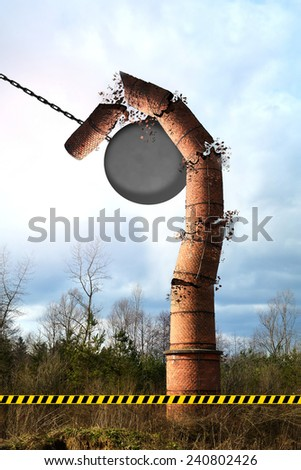 Old chimney hit by a wrecking ball, falling down. - stock photo