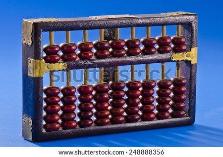 Old chinese abacus on blue background. - stock photo