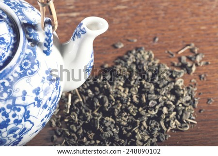 Old Chinese porcelain teapot, with green tea on the wooden desk with soft blue filter - stock photo
