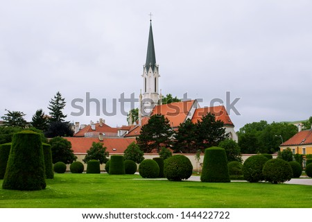 Old church behind the green city park - stock photo