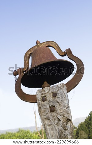 Old church bell on a wooden pole contrasted against a blue sky - stock photo