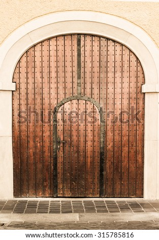 old church wood textured door with stone arch facade - stock photo