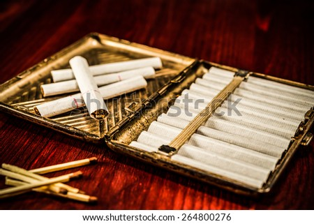 Old cigarette case with cigarettes and matches on a table in mahogany. Focus on the cigarette, image vignetting  - stock photo