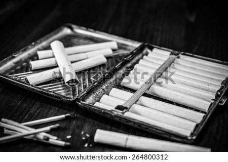 Old cigarette case with cigarettes and matches on a table in mahogany. Focus on the cigarettes, image vignetting and black and white tones - stock photo