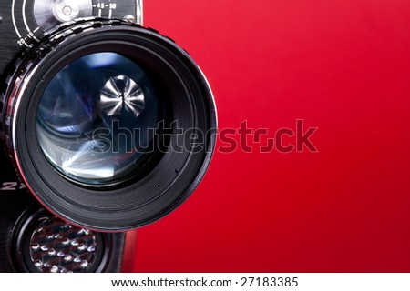 old cinema camera on red background - stock photo