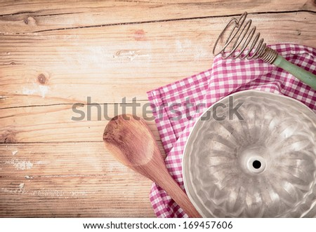 Old circular metal baking mould for cooking a ring cake or flan lying upside down on a fresh red and white checked cloth on a rustic wooden table, overhead view - stock photo