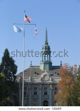 Old City Hall, Berkeley, California, with flagpole flying United States, United Nations (UN), and California State flags. - stock photo