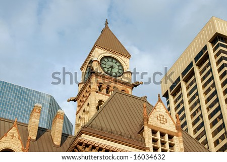 Old city hall of toronto in gothic style between modern skyscrapers under the sunset light - stock photo