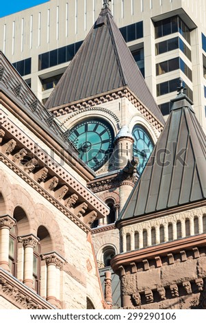 Old city hall Toronto, tower with clock, against a backdrop of a modern building, gothic architecture contrasting with the contemporary - stock photo