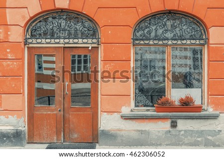 Old city vintage elements. Rounded decorated door with rounded window on a red building facade wall. Historical city elements. Classic european architecture. Luxury estate rent sale concept.