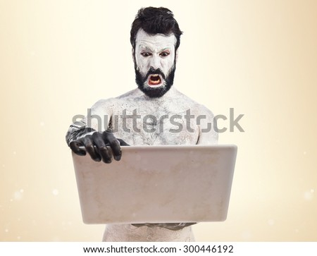 Old civilisation man with laptop over ocher background - stock photo