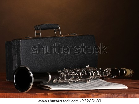 old clarinet, case and notebook with notes on wooden table on brown background - stock photo
