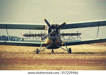 Old classic Antonov (AN-2) cornhusker plane on the field  - stock photo