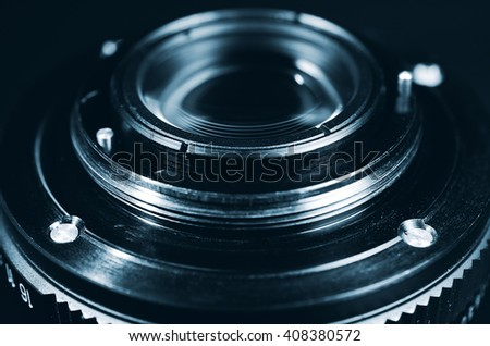 Old classic metal lens from the camera. Detail of the rear part. Selective focus. Close up view. Vintage photo toning. - stock photo