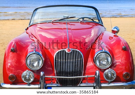 Old classic red car at the beach - stock photo