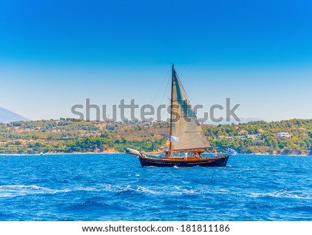 Old classic wooden Greek boat (Kaiki) with sails during a Classic Boats Regatta in Spetses island in Greece - stock photo