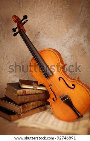 Old classical violin with antique books and grungy sheet music - stock photo