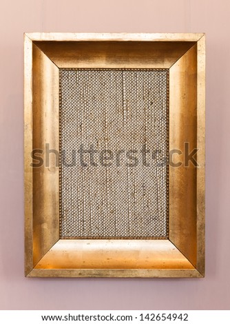 Old classical wooden frame with blank canvas on hanging the wall - stock photo