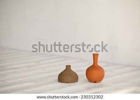 Old clay ceramic vase in white wooden floor and wall background. - stock photo