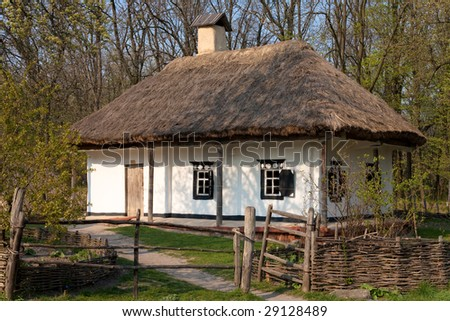 Old clay house with straw roof - stock photo
