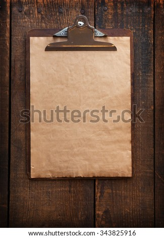 Old clipboard on grungy wooden surface.