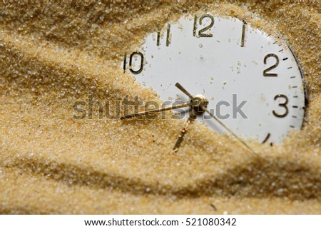 Old clock face in sand close up