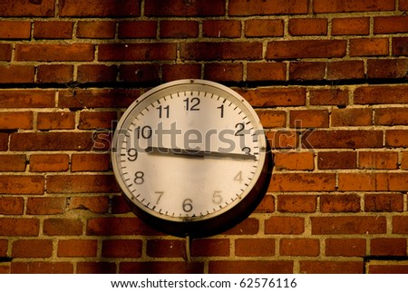 Old clock in evening light at factory - stock photo