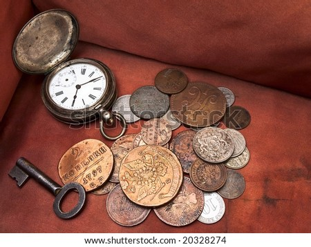 Old clock, key and coins in chest - stock photo