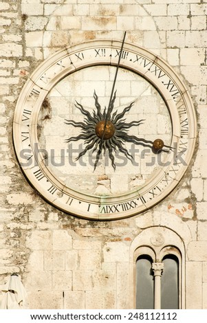 Old  clock on a stone wall - stock photo