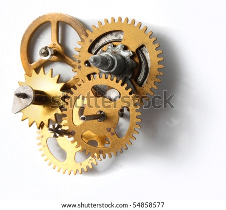 Old clockwork mechanism with brass metal cogs on white background - stock photo