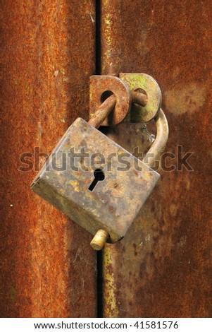 Old closed padlock on the rusty iron door - stock photo
