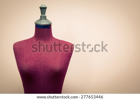 Old clothing mannequin with cement wall background - stock photo