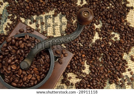Old Coffee Grinder and beans with Burlap. - stock photo