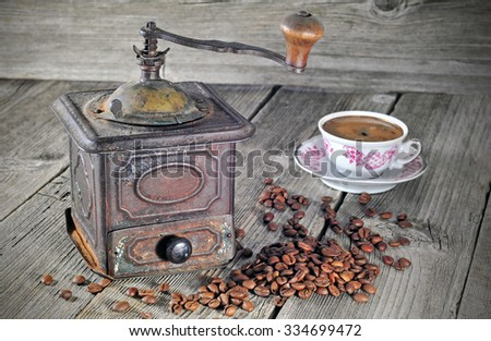 Old coffee grinder with coffee beans and cup of coffee - stock photo
