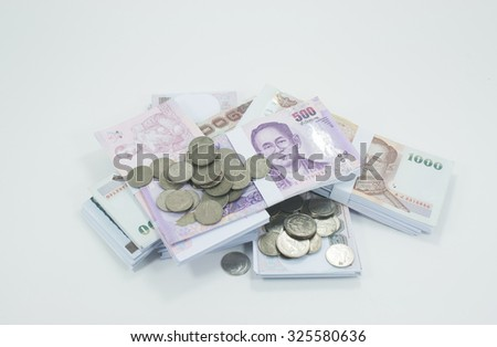 Old coins lay on a pile of banknotes on a white background.