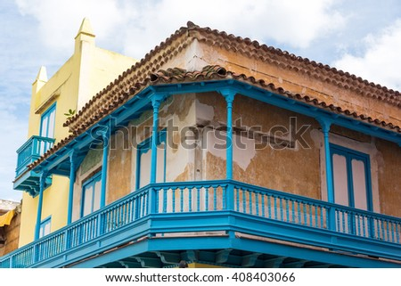 Old colonial architecture with clay tiled roof. House with vintage wooden blue balcony in Cuba. - stock photo