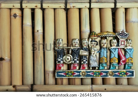 Old colored balinese people figures during hindu ceremony on the bamboo wall