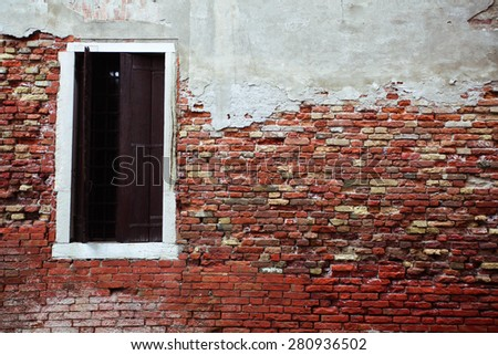 Old colorful brick wall with a door opened. Venice, Italy.