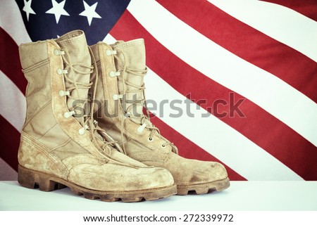 Old combat boots with American flag in the background. Vintage filter effects. - stock photo