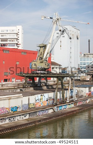 Old commercial dock with rusty cranes at the Rhine river bank in Basel/Switzerland. - stock photo