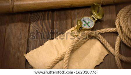 old compass and rope on the background of old weathered wood - stock photo